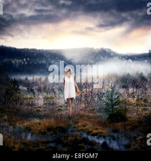 Norway, Woman standing on swamp - Stock Photo