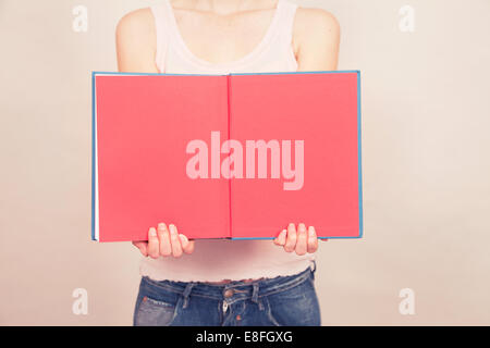 Woman holding book open with blank pages - Stock Photo