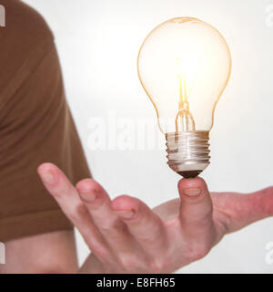 Man with bulb balancing on finger - Stock Photo