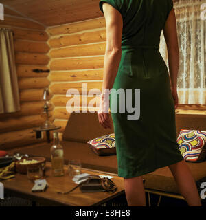 Canada, Alberta, Cochrane, Rear view of woman in mid-century styled log cabin wearing retro dress - Stock Photo