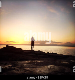 Rear View Of A Woman Standing By The Sea - Stock Photo