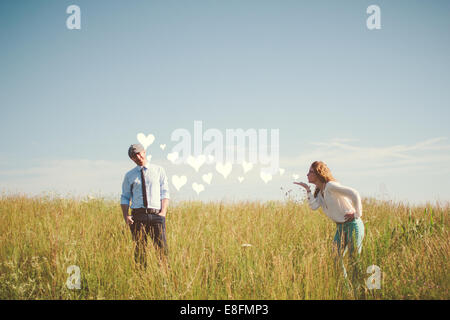 USA, Tennessee, Davidson County, Nashville, Couple blowing hearts on meadow - Stock Photo