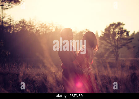 Netherlands, Portrait of couple standing in meadow - Stock Photo