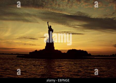 USA, New York State, New York City, Statue of Liberty at sunset - Stock Photo