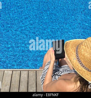 Woman holding tablet sitting with feet in swimming pool - Stock Photo