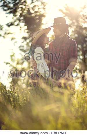 Cowboy and cowgirl couple in field - Stock Photo