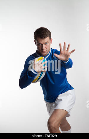 Rugby player running with rugby ball - Stock Photo