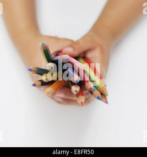 Child's hands holding colored pencils - Stock Photo