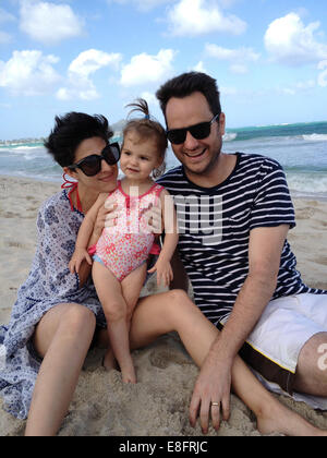 Mother, Father and daughter (18-23 months) sitting on beach - Stock Photo