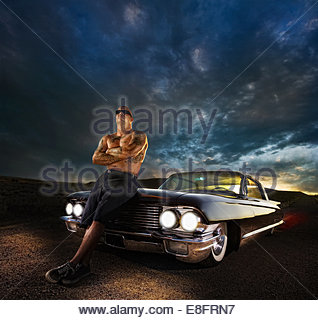 Tattooed man leaning against his vintage car - Stock Photo