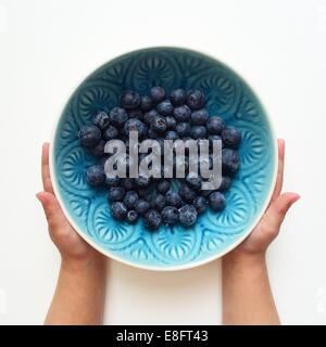 Boy holding a bowl of blueberries - Stock Photo