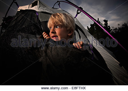 Scared boy looking out of tent opening at night, Colorado, America, USA - Stock Photo