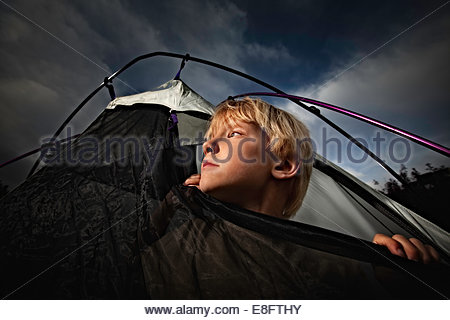 Boy looking out of tent opening at night, Colorado, America, USA - Stock Photo