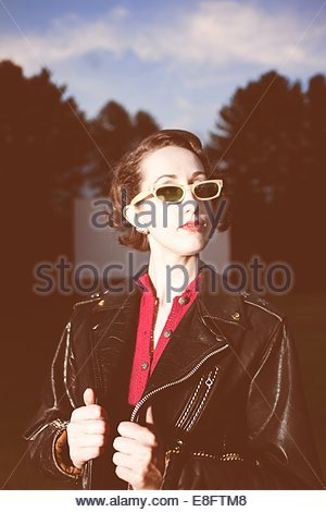 Young woman wearing sunglasses and leather jacket outdoors - Stock Photo
