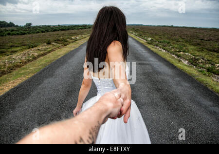 View of couple on long road - Stock Photo