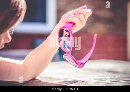 Girl reflecting in sunglasses - Stock Photo