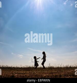 Silhouette of two girls playing in  a meadow - Stock Photo