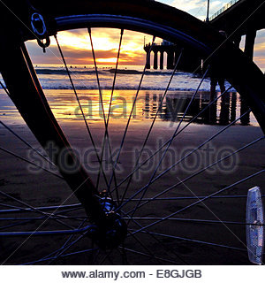 Ocean through bike wheel at sunrise - Stock Photo