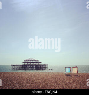 UK, England, East Sussex, Brighton, Two deck chairs on Brighton Beach - Stock Photo
