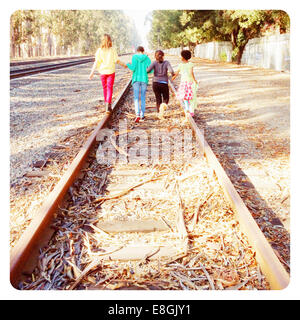 Four children walking along tracks - Stock Photo