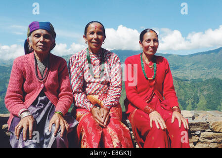 Nepal, Portrait of women sitting on stone wall in mountains - Stock Photo