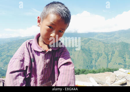 Nepal, Portrait of boy (10-11) sitting on stone wall in mountains - Stockfoto