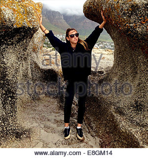 Woman standing on beach between rocks - Stock Photo
