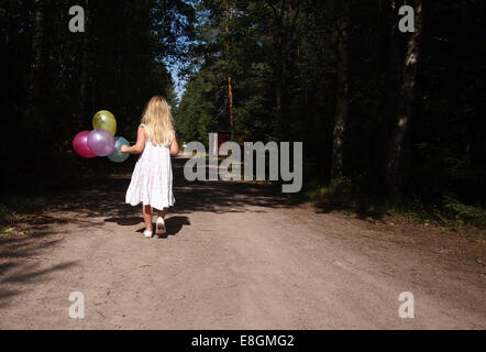 Girl (6-7) in white dress walking with balloons in her hand - Stock Photo