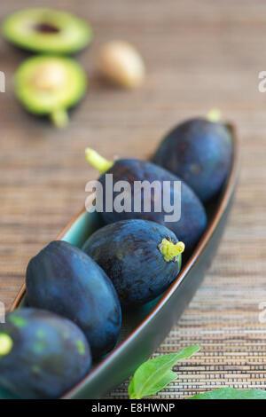 Avocado Früchte in Keramikschale auf gewebte Matte - Stockfoto