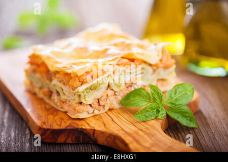 Fish and broccoli mousse lasagne on a wooden table - Stock Photo