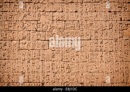 Wall full of sunk relief of hieroglyphics -temple King Ramses III (City of Habu) West of luxor 1100 B.C - Stock Photo
