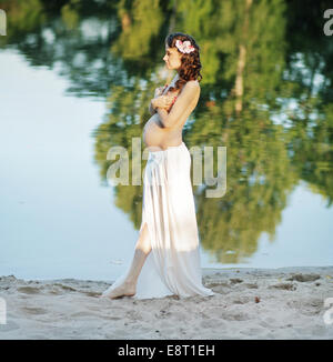 Pregnant woman walking on the beach - Stockfoto