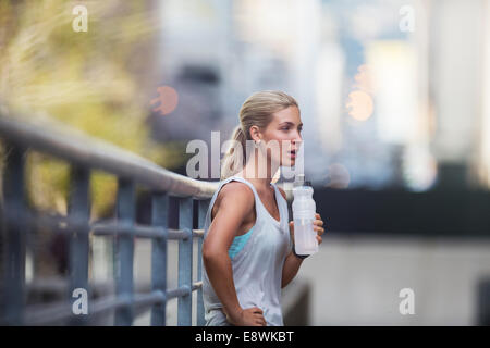 Woman resting after exercising on city street - Stock Photo
