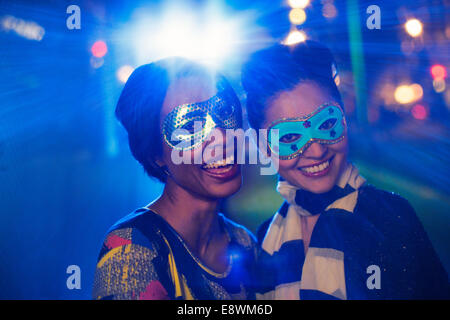 Women in masks smiling together - Stock Photo