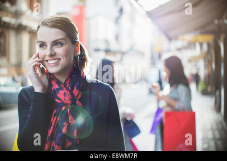 Woman talking on cell phone on city street - Stock Photo