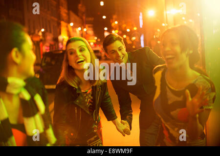 Friends walking down city street together at night - Stock Photo