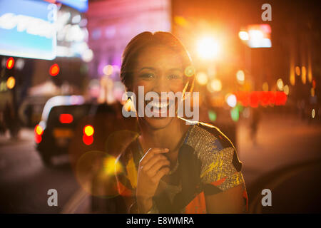 Woman smiling on city street at night - Stock Photo