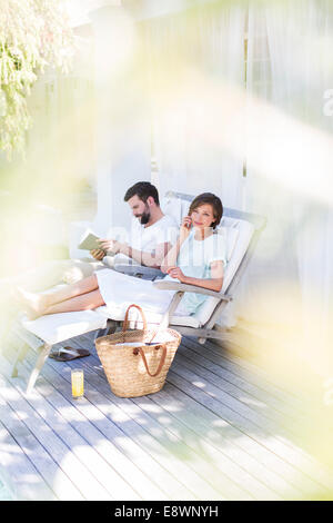 Couple relaxing in lawn chairs on wooden deck - Stock Photo