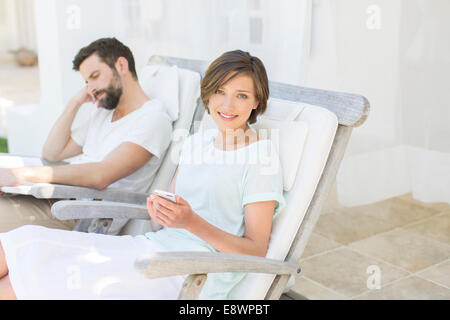 Couple relaxing in lawn chairs outdoors - Stock Photo