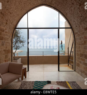 View through arched window to woman standing on balcony with view to sea building, T House, Israel, Middle East. - Stock Photo