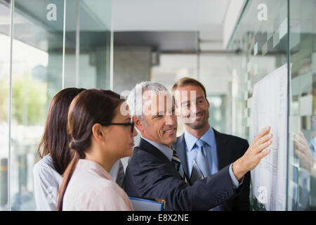 Business people discussing documents in office building - Stock Photo