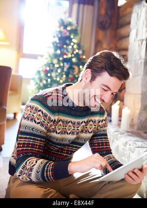 Man using digital tablet in log cabin - Stock Photo