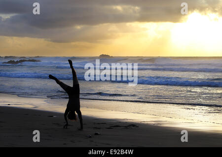 Man doing cartwheels on the beach in Castlejo, Costa Vicentina, Portugal - Stock Photo