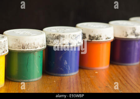 Some old cans with gouache of different color - Stock Photo