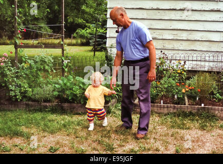 grandfather helping toddler grandson to walk - Stock Photo