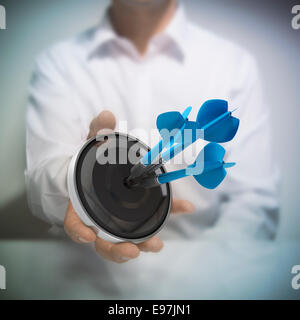 Man holding on black target with three blue darts hitting the center. Concept image for illustration of Marketing - Stock Photo