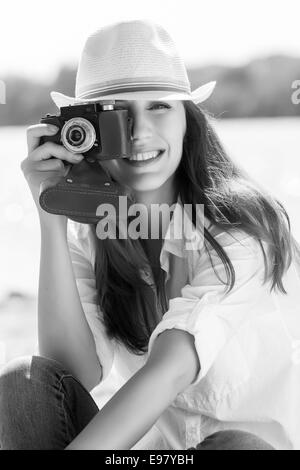 Young pretty woman taking a photography at the beach in summer midday - Stock Photo