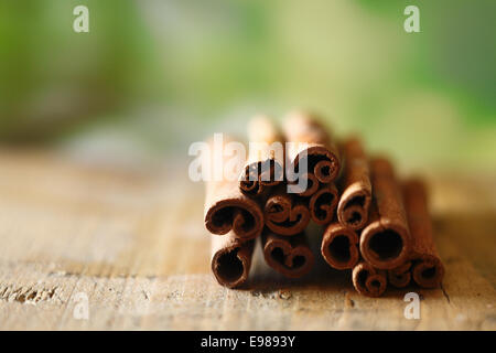 Closeup of a bunch of dried spicy cinammon sticks on a wooden surface with copyspace - Stock Photo