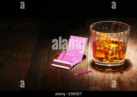 Whiskey on the Rocks or Scotch with a book of matches with a phone number insight - Stock Photo