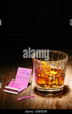 Romantic tryst on a matchbook alongside a glowing glass of whiskey on an old wooden counter in a nightclub - Stock Photo